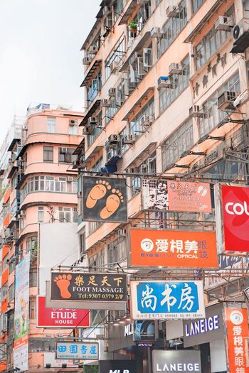 Low angle view of advertisements against buildings in city
