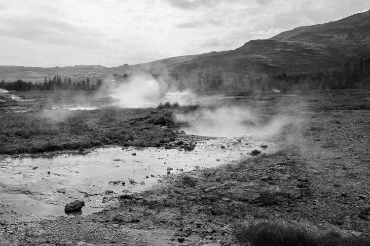 Steam Emitting From Hot Spring Against Mountain