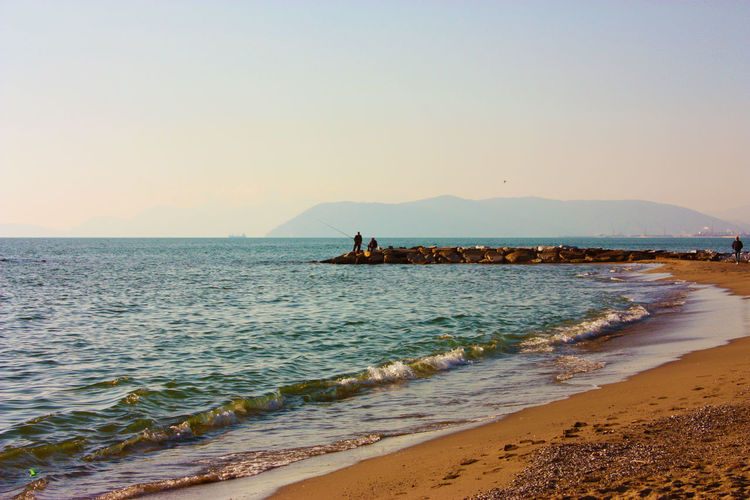 Rocks lined up on the sea water in front of the beach at sunset in versilia and bright colors