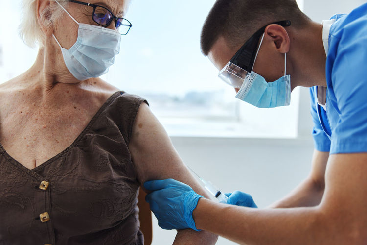 Doctor wearing mask vaccinating woman