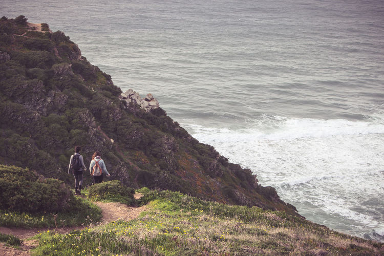 Rear view of hikers walking on mountain against sea