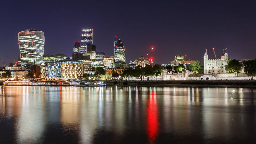 Modern illuminated buildings by lake against sky in city at night