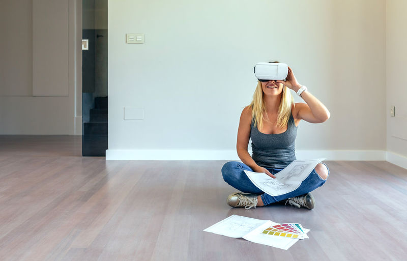 Young woman watching the decoration of her house with virtual reality glasses Blonde Copy Space Decorating Glasses Happiness Happy Horizontal Virtual Reality Woman Caucasian Color Decoration Female Girl Home Interior Lifestyles New Home One Person Palette Plans Virtual Glasses Vr Watching Young Adult Young Women