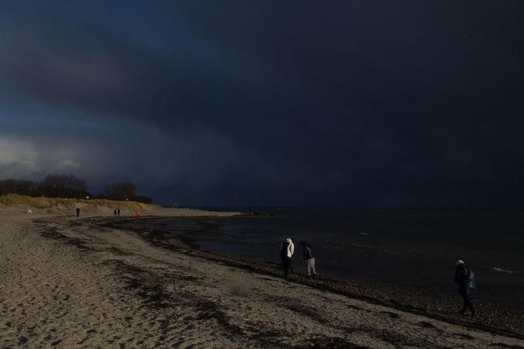 People walking on beach against sky at dusk