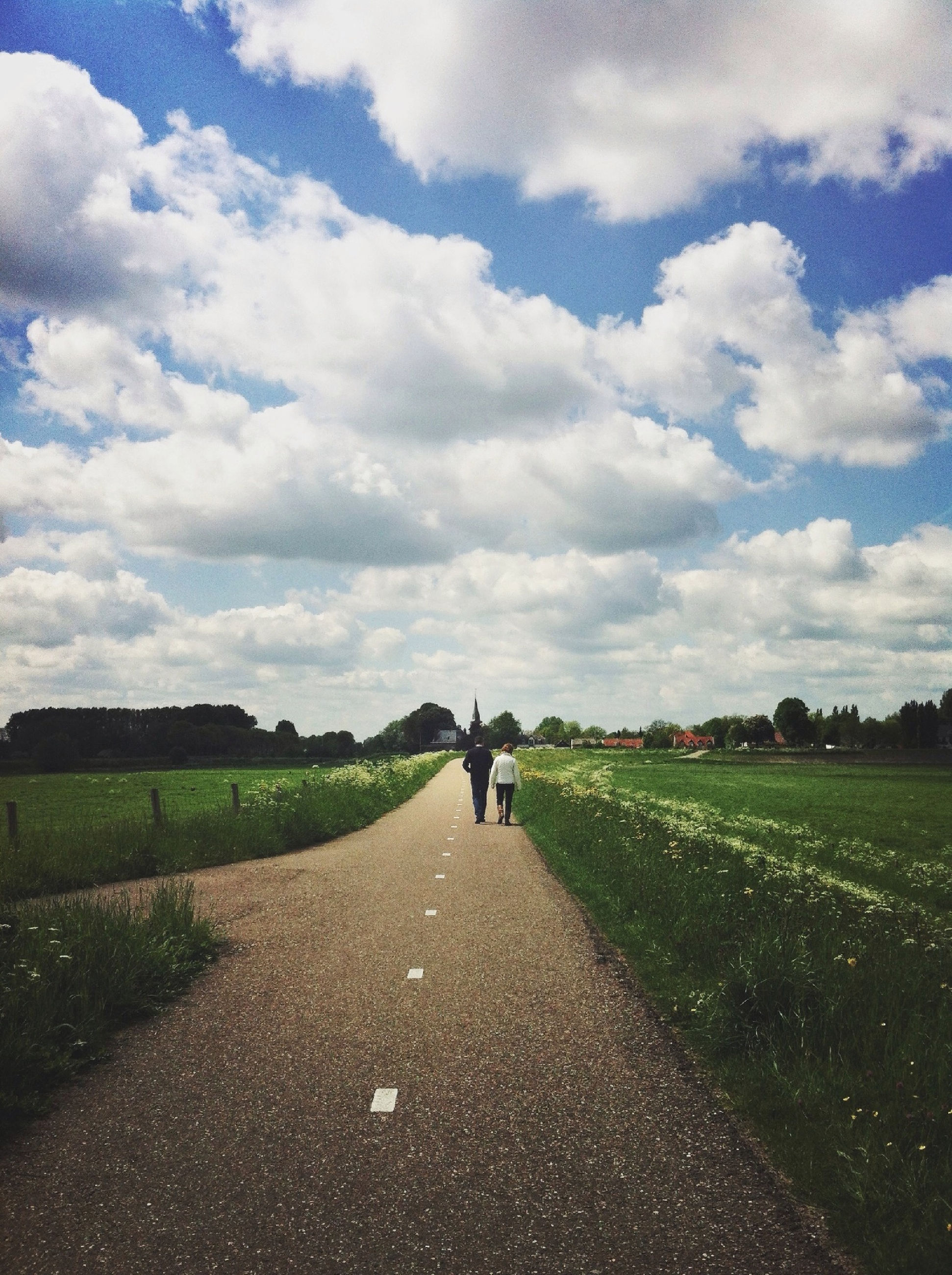 sky, the way forward, grass, field, cloud - sky, landscape, rear view, walking, full length, road, tranquility, cloud, diminishing perspective, tranquil scene, men, cloudy, nature, lifestyles