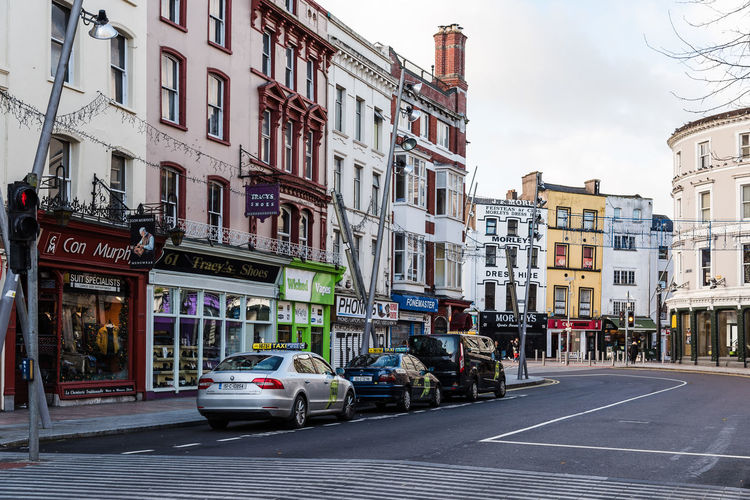 St Patrick Street in City Center of Cork Architecture City Cityscape Commercial Street Shopping Travel Architecture Building Exterior Built Structure Car City Commercial County Day Irish Land Vehicle Mode Of Transport No People Outdoors People Residential Building Road Shop Sky St Patrick Store Street Transportation Urban