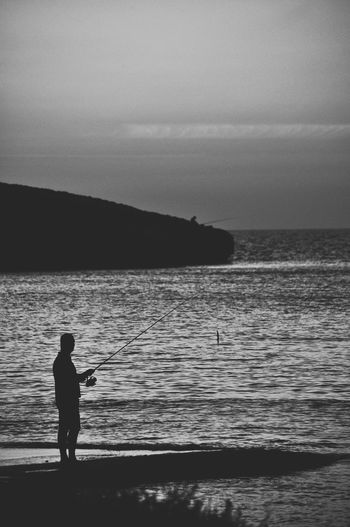 Silhouette man standing on sea shore against sky