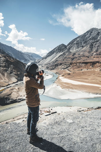 Full length of man photographing on mountain against sky