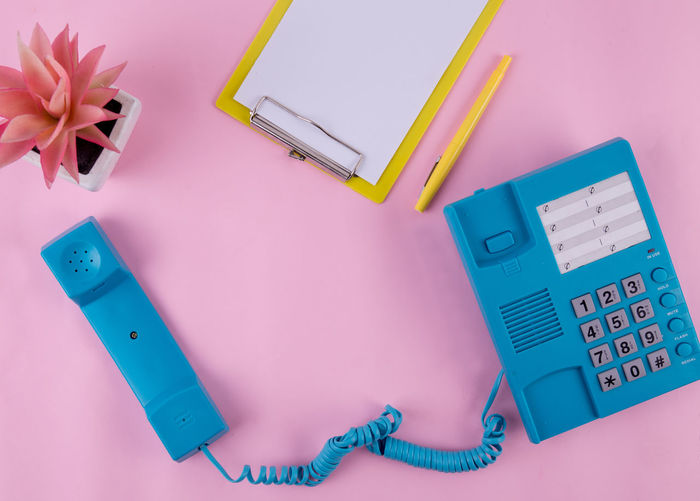 Directly above shot of landline phone with clipboard on pink background