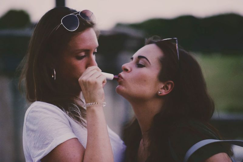 Close-Up Of Woman Applying Lipstick To Friend Outdoors