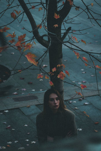 Portrait of young woman with autumn leaves
