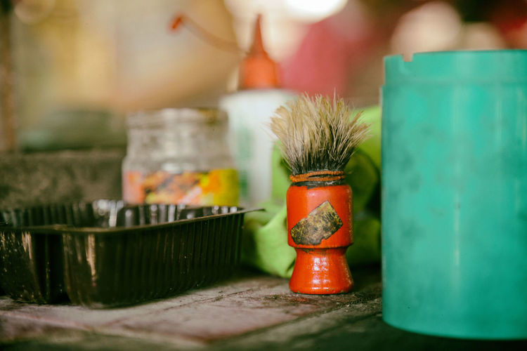 Close-up of shaving brush by containers on table