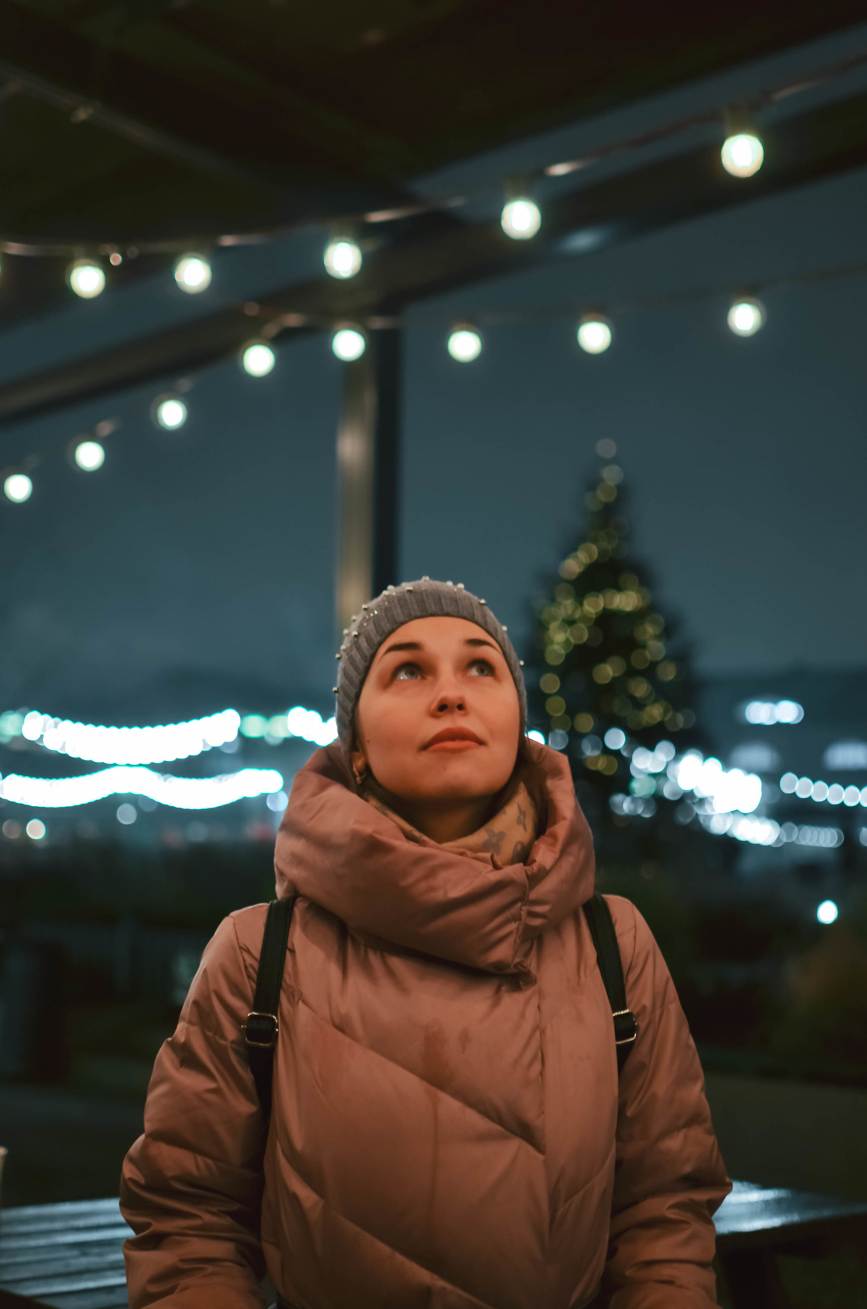 illuminated, front view, one person, young adult, clothing, waist up, real people, standing, indoors, night, lighting equipment, lifestyles, looking, warm clothing, leisure activity, winter, portrait, focus on foreground, light, hairstyle