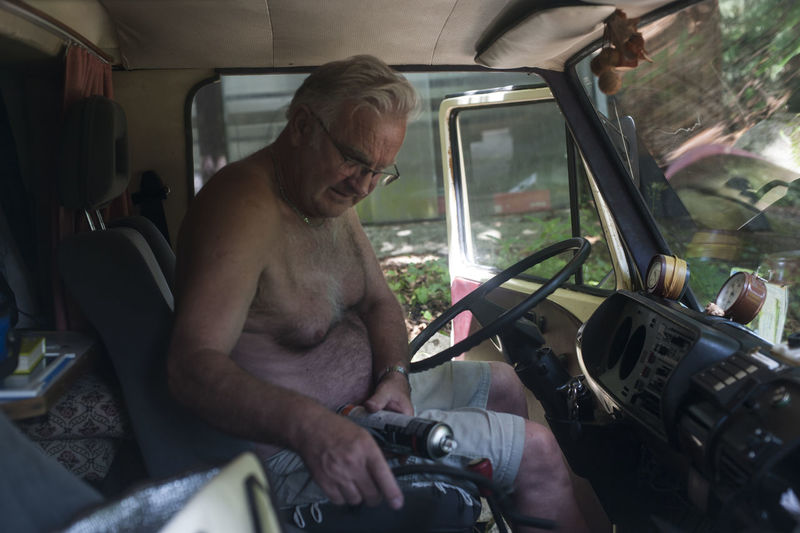 Shirtless Man Sitting In Car