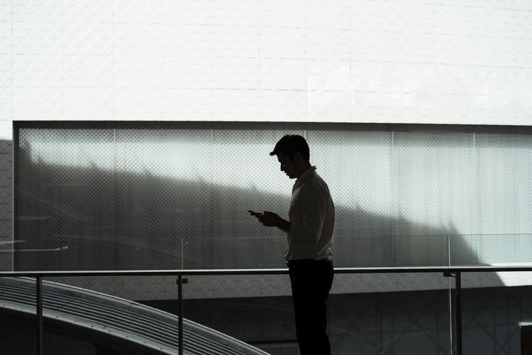 Side view of man using mobile phone against wall