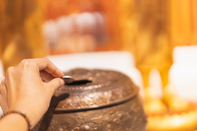 hand insert coin to make merit, selective focus, buddhist culture concept Asian  Bright Buddha Buddhism Buddhist Ceremony Coin Culture Day Focus Golden Hand Holy Insert Light Merit Monk  Pagoda Religion Selective Statue Symbol Temple Thai Thailand Yellow