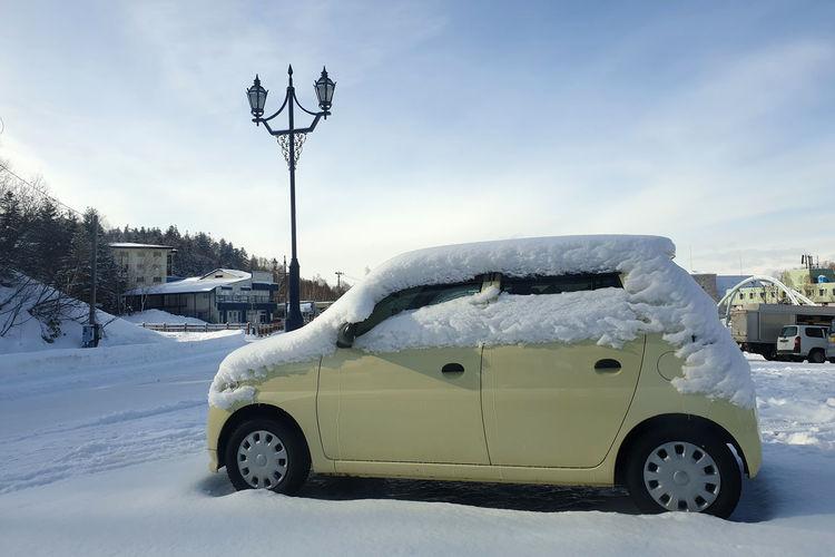 Snow covered car on street against sky