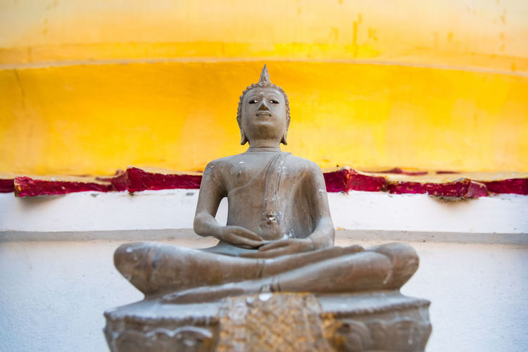 Low angle view of buddha statue against yellow wall