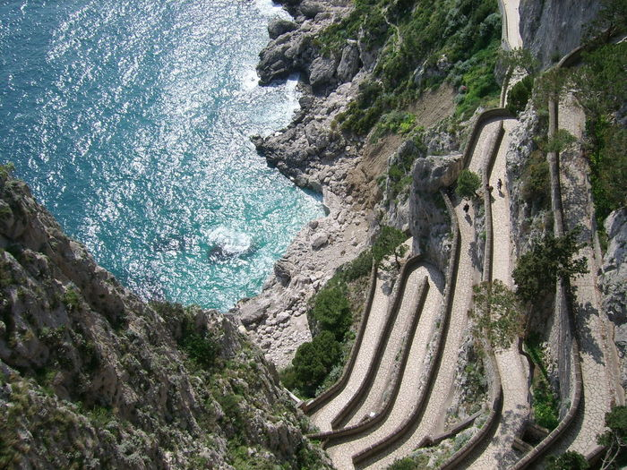 High Angle View Of Road By Sea Against Mountains
