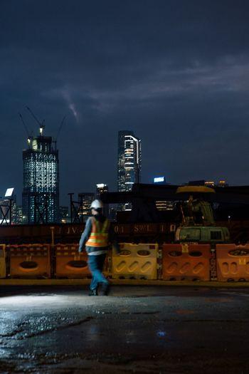 Full length of woman standing on illuminated city street at night