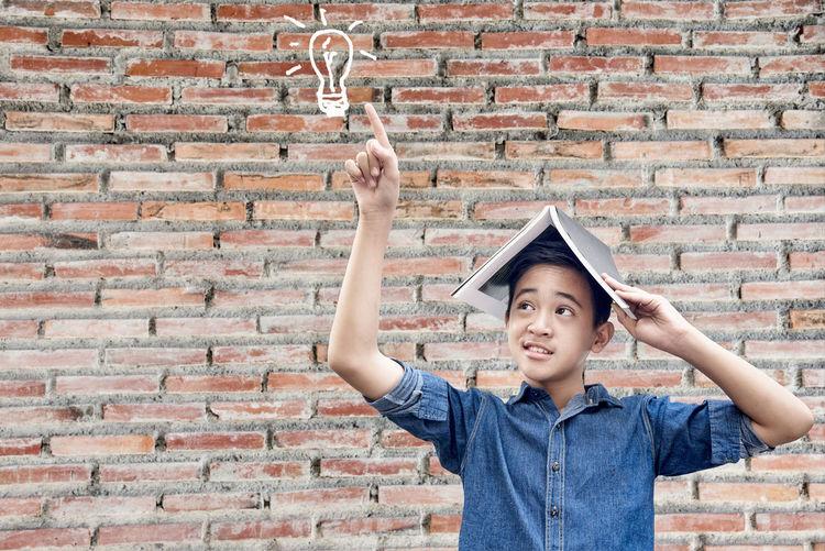 Portrait of boy holding stone against brick wall
