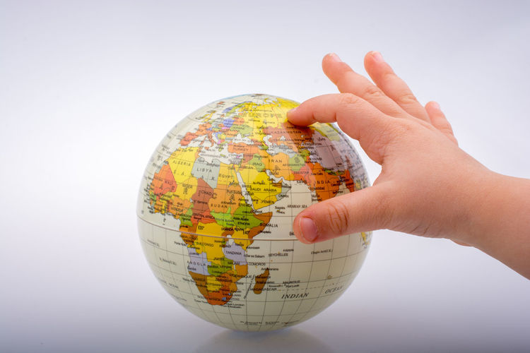 Close-up of hand holding globe against white background
