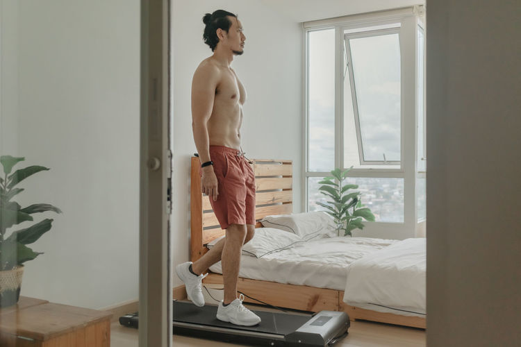Full length of shirtless man standing on bed at home