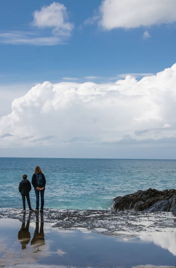 Rear View Of Woman With Son Standing At Sea Shore Against Sky