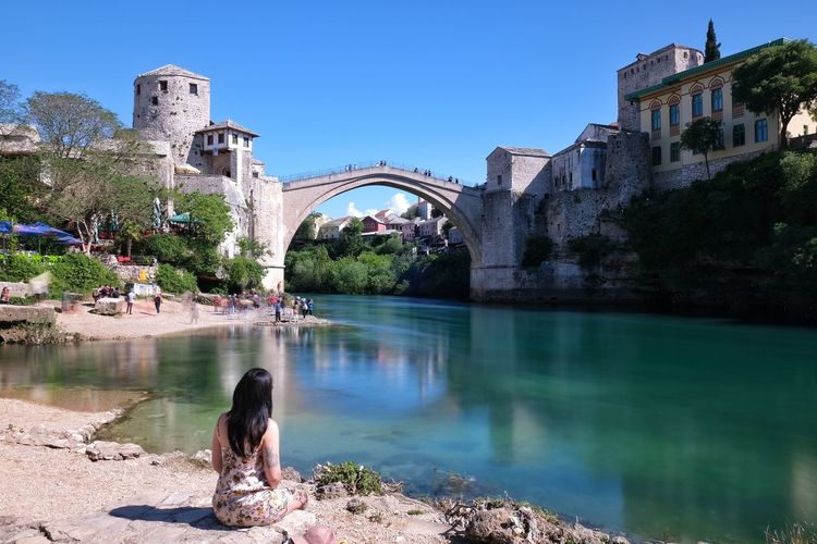 Woman on bridge over river against sky