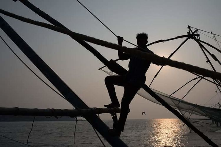 Silhouette of person on swing at sea