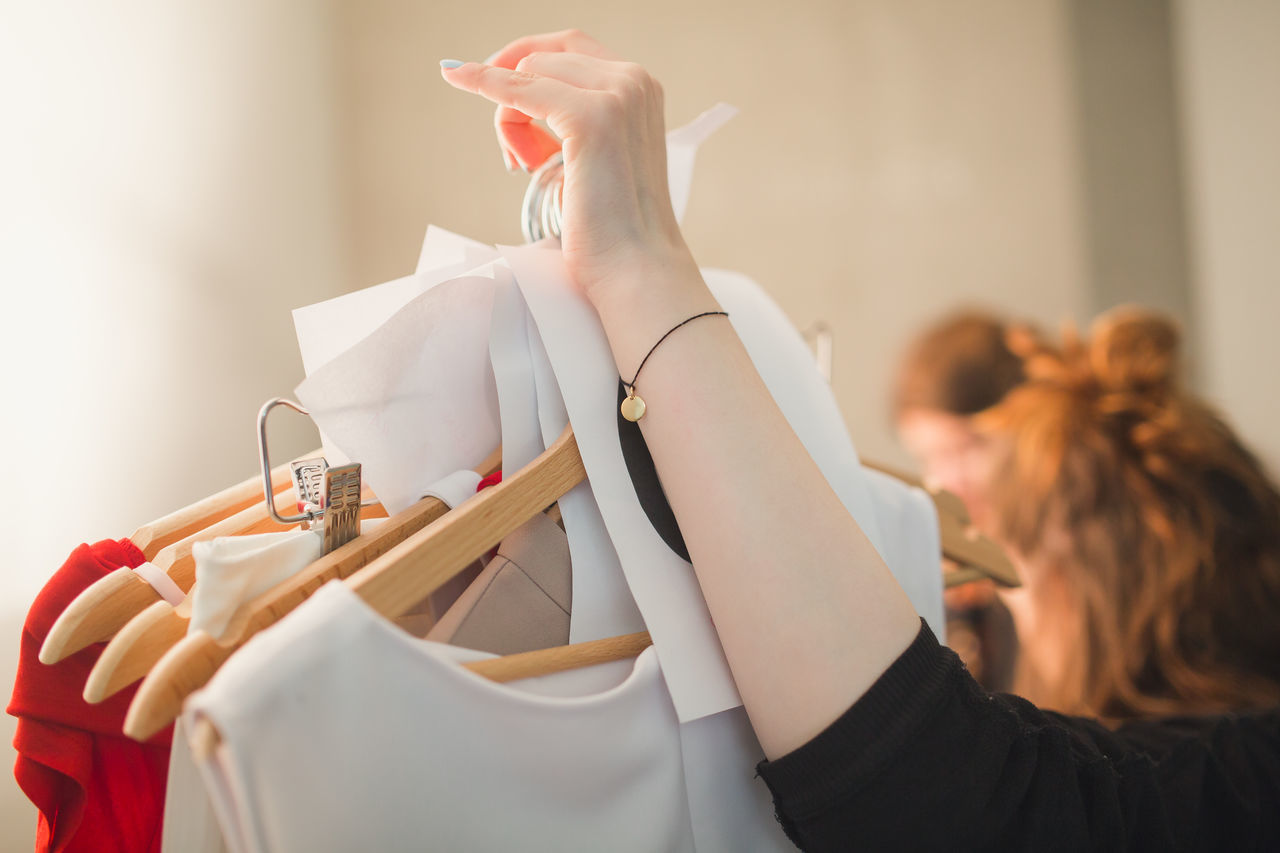Cropped Image Of Woman Holding Clothes Hanging From Coathangers