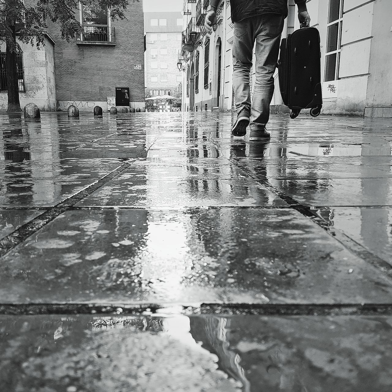 LOW SECTION OF WOMAN WALKING ON WET FOOTPATH IN CITY DURING MONSOON