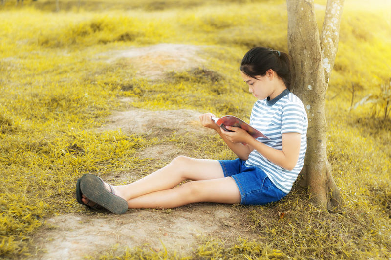 Full Length Of Girl Reading Book While Sitting On Field