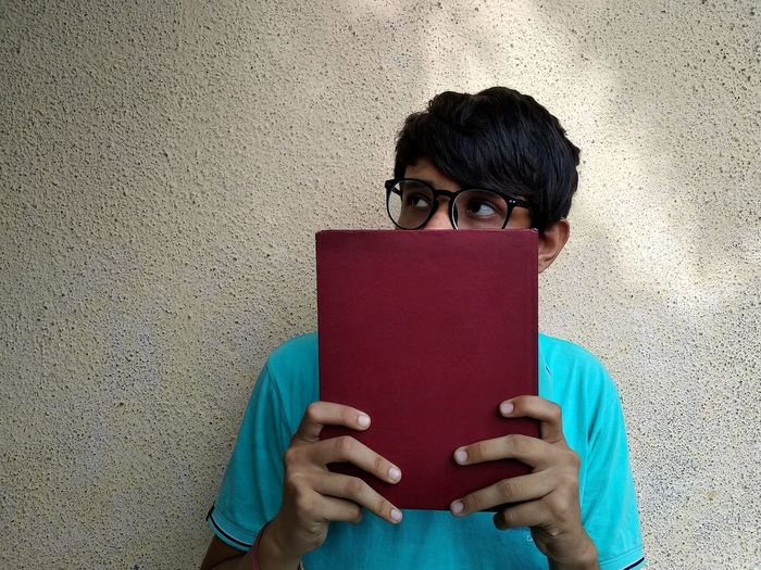 Thoughtful man holding book while standing against wall