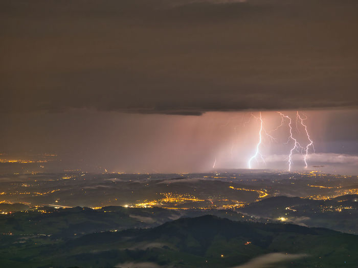 Aerial view of illuminated cityscape against dramatic sky and lightning
