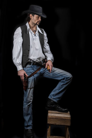 Handsome young man. This is an American cowboy. A vow to a white shirt, brown waistcoat and blue jeans. Black shoes on the feet. Carries a shtyapa, on a belt two pistols. The hair is of medium length; on the face is a beard and mustache. Authentic photo. Culture of America. Cowboy Wild West America American Gun National Authentic Moments Lifestyles Lifestyle One Person Candid Authentic Hat Clothing Black Background Front View Men Casual Clothing Adult Standing Young Adult Young Men Full Length Males  Jeans