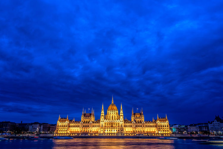 Illuminated hungarian parliament building and danube river in city at dusk