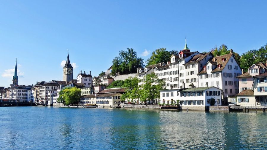 Limmat river by buildings and churches in city against blue sky