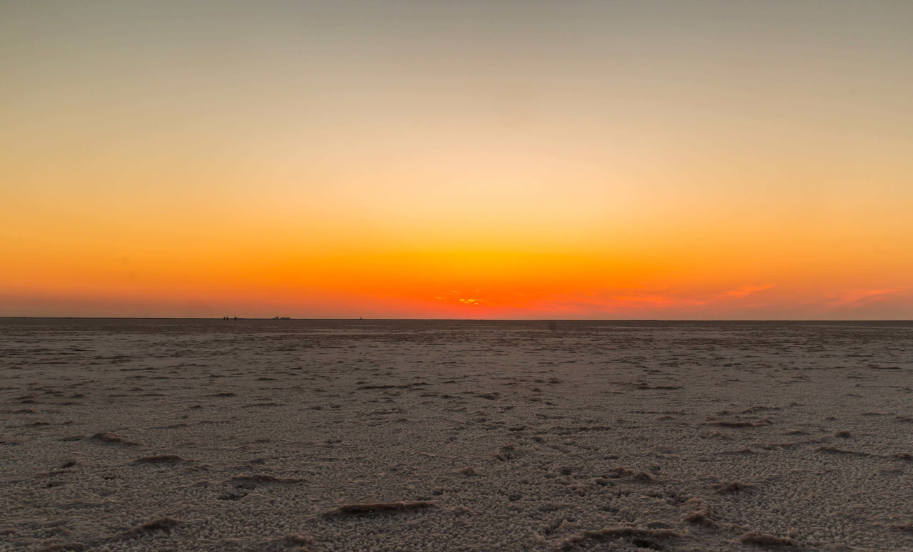 sunset, nature, tranquility, beauty in nature, sea, scenics, sand, beach, orange color, tranquil scene, sky, horizon over water, outdoors, no people, water, landscape, clear sky, day