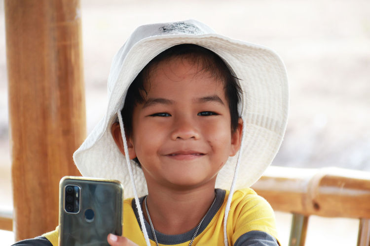 Portrait of cute boy holding smart phone outdoors