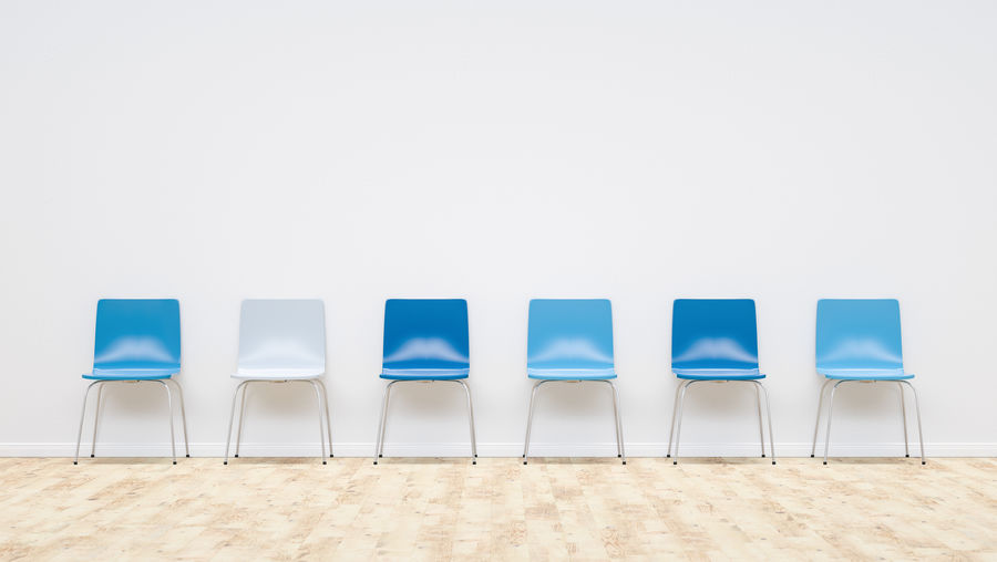 Empty blue chairs in room against wall