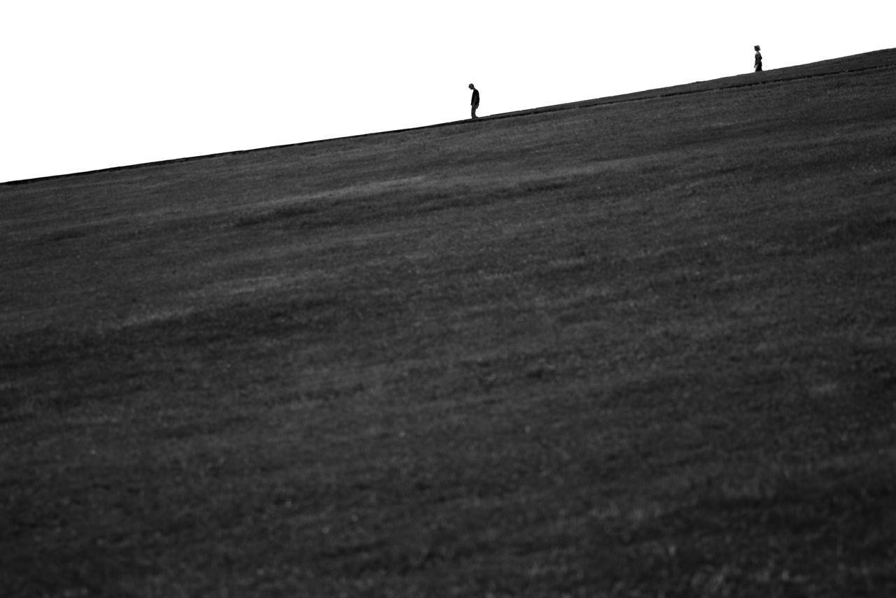 SURFACE LEVEL OF PEOPLE WALKING ON LANDSCAPE