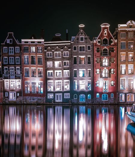 Reflection of illuminated buildings in city at night, amsterdam