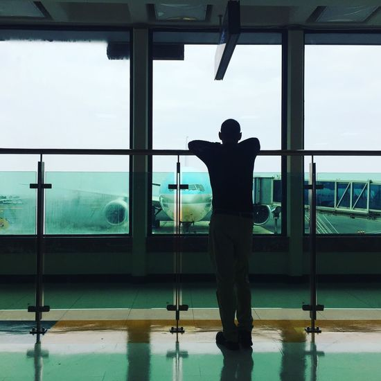 Rear view of silhouette man standing by window at airport