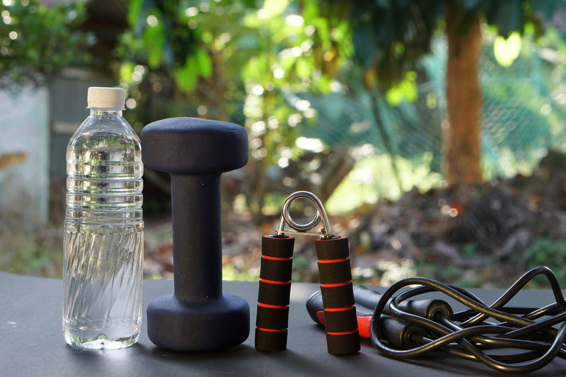 Plain water drink, dumbbell, hand grip, skipping rope. Training, fitness equipment. Exercising Grip Isolated Close-up Day Drink Dumbbell Hand Health Healthy Healthy Eating Healthy Lifestyle Indoors  No People Outdoors Sport Sports Training