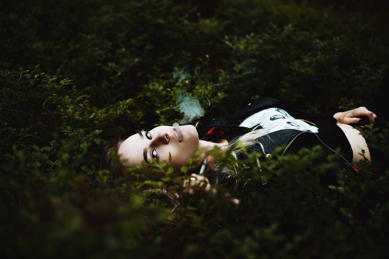Portrait Of Young Woman Smoking While Lying On Plants