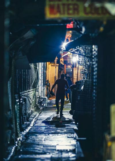 Rear view of man walking on footpath amidst buildings in city