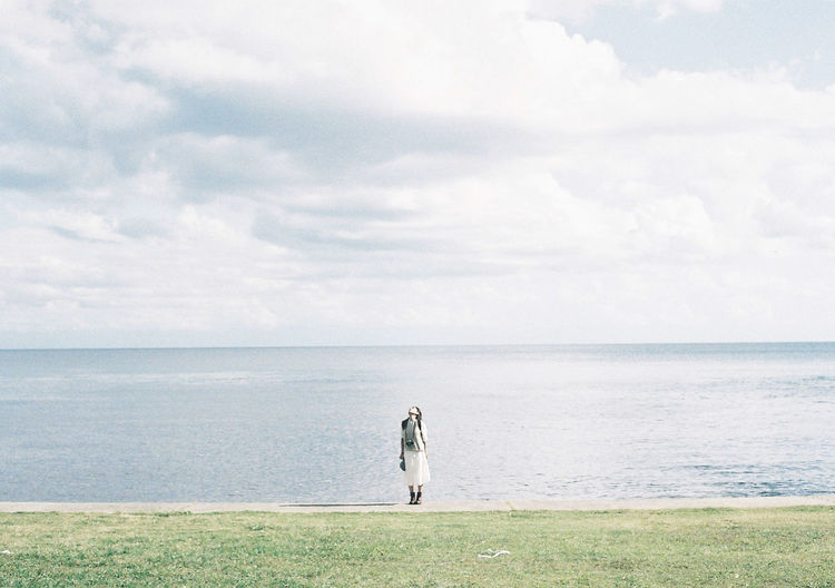 Woman standing on sea shore against sky