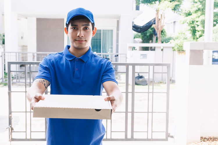Portrait of salesman with cardboard box standing at gate way