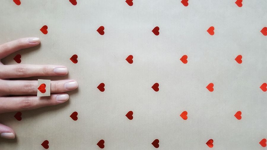 Cropped Image Of Woman Hand On Paper With Heart Shapes